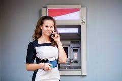 Ung kvinna som sätter in en kreditkort till ATM royaltyfria bilder