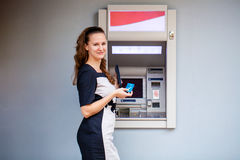 Ung kvinna som sätter in en kreditkort till ATM royaltyfria foton