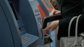 Ung kvinna som sätter in en kreditkort till ATM, härliga flickabankrörelsen, affärskvinna efter arbete i banken, shoppinggalleria arkivfilmer