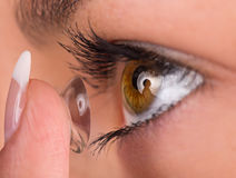 Ung kvinna som sätter kontaktlinsen i hennes öga Royaltyfri Fotografi