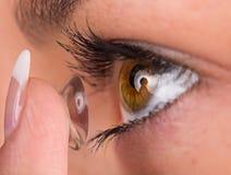 Ung kvinna som sätter kontaktlinsen i hennes öga Arkivfoton
