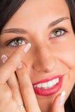 Ung kvinna som sätter kontaktlinsen i hennes öga Arkivbild
