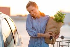 Ung kvinna som sätter livsmedel på bilstammen royaltyfria bilder