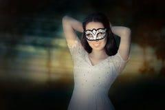 Ung kvinna som sätter på en maskering royaltyfri fotografi