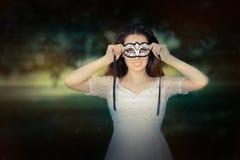 Ung kvinna som sätter på en maskering arkivfoto