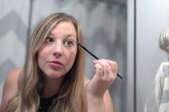 Ung kvinna som sätter på makeup fotografering för bildbyråer
