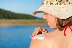 Ung kvinna som sätter sollotion på sommarsemester fotografering för bildbyråer
