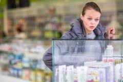 Ung kvinna som söker efter de högra preventivpillerarna i ett modernt apotek Royaltyfria Bilder