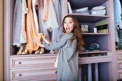 Ung kvinna som söker vad för att bära i en garderob Arkivfoton