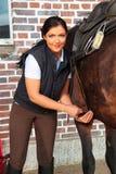 Ung kvinna som sadlar hennes häst Royaltyfria Bilder