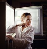 Ung kvinna som sent söker efter något mellanmål i kyl på natten fotografering för bildbyråer
