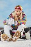 Ung kvinna som ser bort medan hållande snowboard i snö Arkivbilder