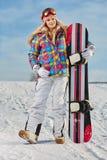 Ung kvinna som ser bort medan hållande snowboard i snö Arkivfoton