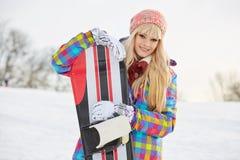 Ung kvinna som ser bort medan hållande snowboard i snö Arkivbild