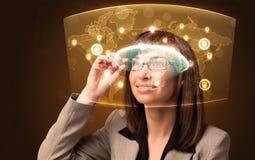 Ung kvinna som ser den futuristiska sociala nätverksöversikten Arkivbilder