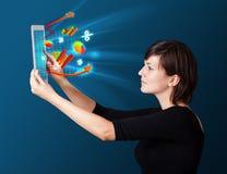 Ung kvinna som ser den moderna minnestavlan med abstrakta ljus och va Arkivbild