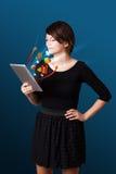 Ung kvinna som ser den moderna minnestavlan med abstrakta ljus och va Arkivfoto