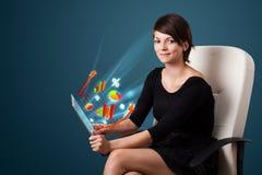 Ung kvinna som ser den moderna minnestavlan med abstrakta ljus och va Royaltyfria Bilder