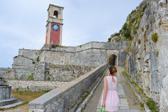 Ung kvinna som ser den stora gamla klockan i en fästning på den Korfu islaen Arkivbilder