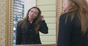 Ung kvinna som ser den utomhus- spegeln lager videofilmer