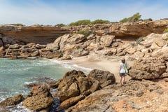 Ung kvinna som ser en härlig liten vik på den medelhavs- kusten royaltyfria foton
