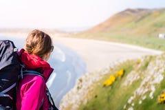 Ung kvinna som ser för att distansera från en Cliff Over The Seashore I Royaltyfri Bild
