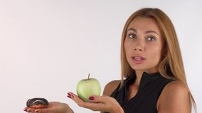 Ung kvinna som ser förväxlat välja mellan sunt och skräpmat royaltyfri fotografi
