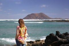 Ung kvinna som ser havet Arkivfoto