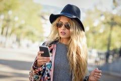 Ung kvinna som ser hennes smartphone i stads- bakgrund Royaltyfri Fotografi