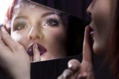 Ung kvinna som ser in i en spegel Royaltyfria Bilder