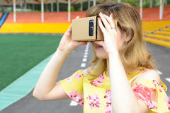 Ung kvinna som ser in i exponeringsglas för en virtuell verklighet Arkivbild