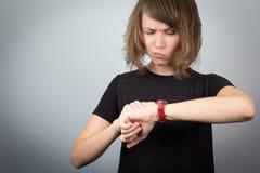 Ung kvinna som ser klockatidwaitnig Arkivfoto