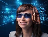 Ung kvinna som ser med futuristiska smarta tekniskt avancerade exponeringsglas Royaltyfri Fotografi