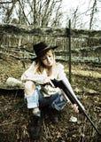 Ung kvinna som ser ner trumman av ett vapen Arkivbild