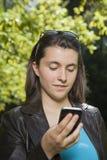 Ung kvinna som ser smartphonen Arkivfoton