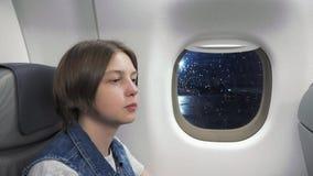Ung kvinna som ser till och med fönster i flygplan arkivfilmer