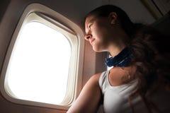 Ung kvinna som ser till och med fönster i flygplan Royaltyfria Foton