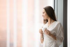 Ung kvinna som ser till och med golvfönstret med en kopp Arkivbilder