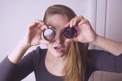 Ung kvinna som ser till och med kameralinsen och leende Fotografihjälpmedel och utrustning royaltyfria foton