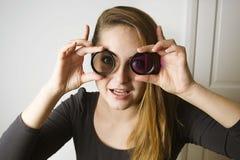 Ung kvinna som ser till och med kameralinsen och leende Fotografihjälpmedel och utrustning royaltyfri foto