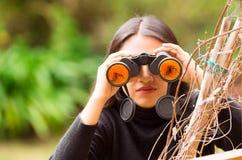 Ung kvinna som ser till och med svart kikare i skogen i en suddig bakgrund royaltyfri foto