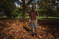 Ung kvinna som ser träd i parkera Royaltyfria Foton