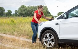 Ung kvinna som ser under huven av den brutna bilen och försöker att fixa den arkivfoton