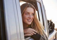 Ung kvinna som ser ut ur öppet passagerarefönster av en bil royaltyfri bild