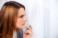 Ung kvinna som ser ut ur fönstret Arkivfoto