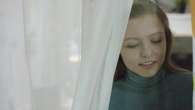 Ung kvinna som ser ut ur fönstret på kamera lager videofilmer