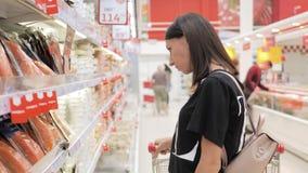 Ung kvinna som shoppar sund mat i supermarket f?rs?ljning, shopping, consumerism och folkbegrepp arkivfilmer