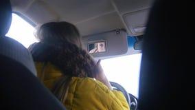 Ung kvinna som sitter i bilen och ser på spegeln fotografering för bildbyråer