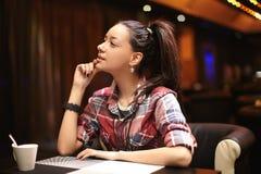 Ung kvinna som sitter i cafen Royaltyfria Bilder