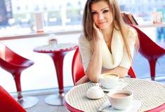 Ung kvinna som sitter i cafen med en kopp av tea Arkivbild
